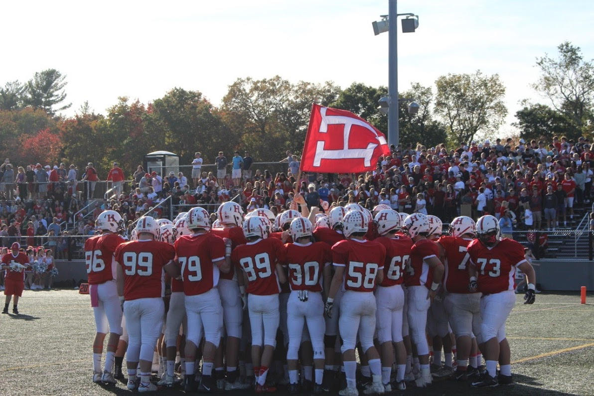 Hingham Harbormen Football holds the Hingham flag before the game against Duxbury.