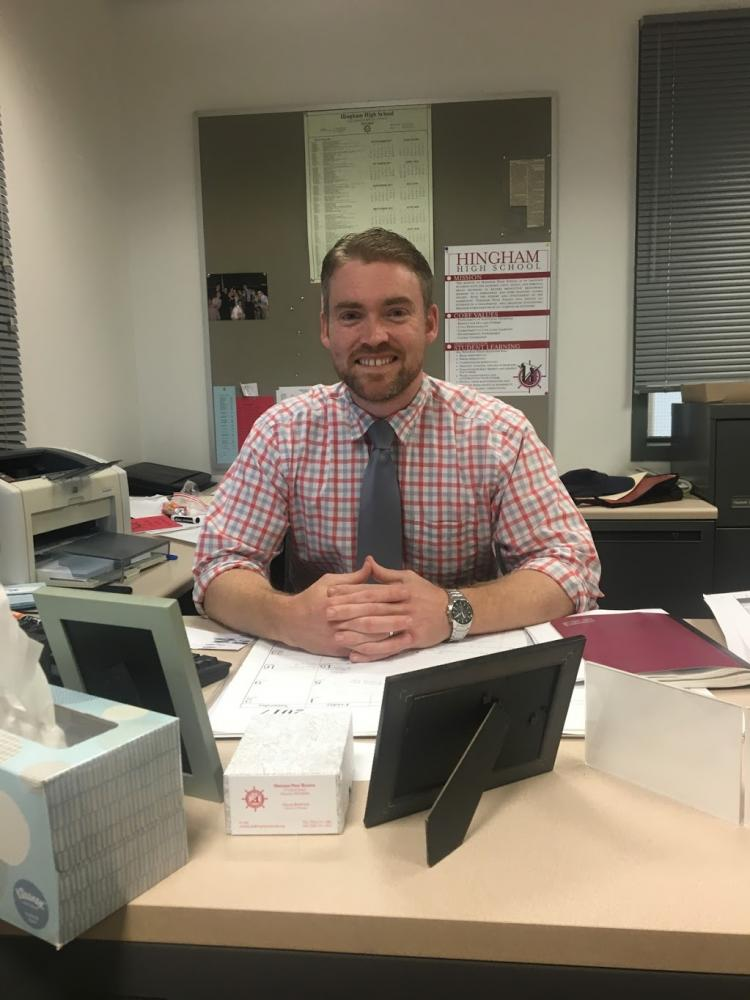 The+vice+president+of+Hingham+High+smiles+behind+his+new+desk.