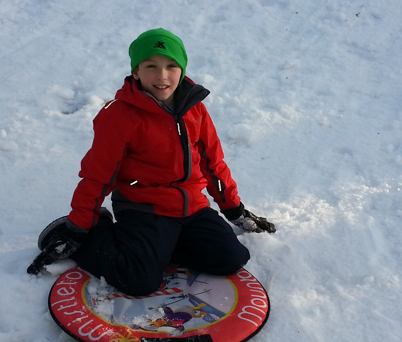 The author's little brother sleds down a snowy slope.