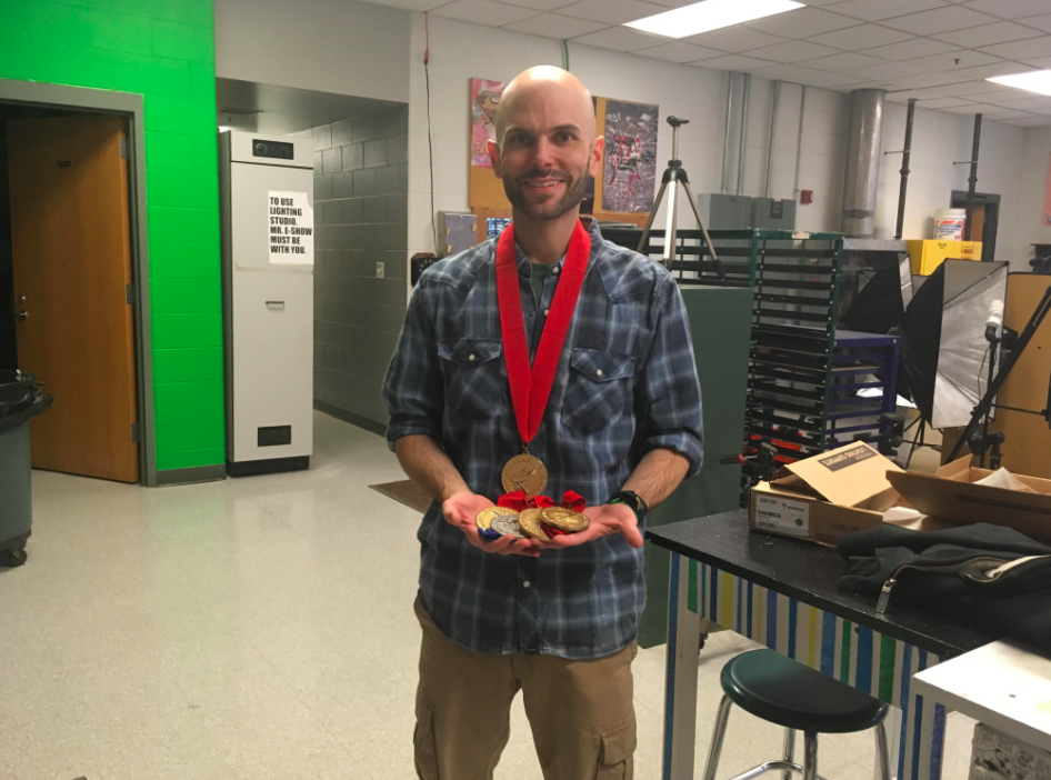Graphic Design teacher Mr. Eshow with past year medals awarded to Hingham High School students at the national awards.