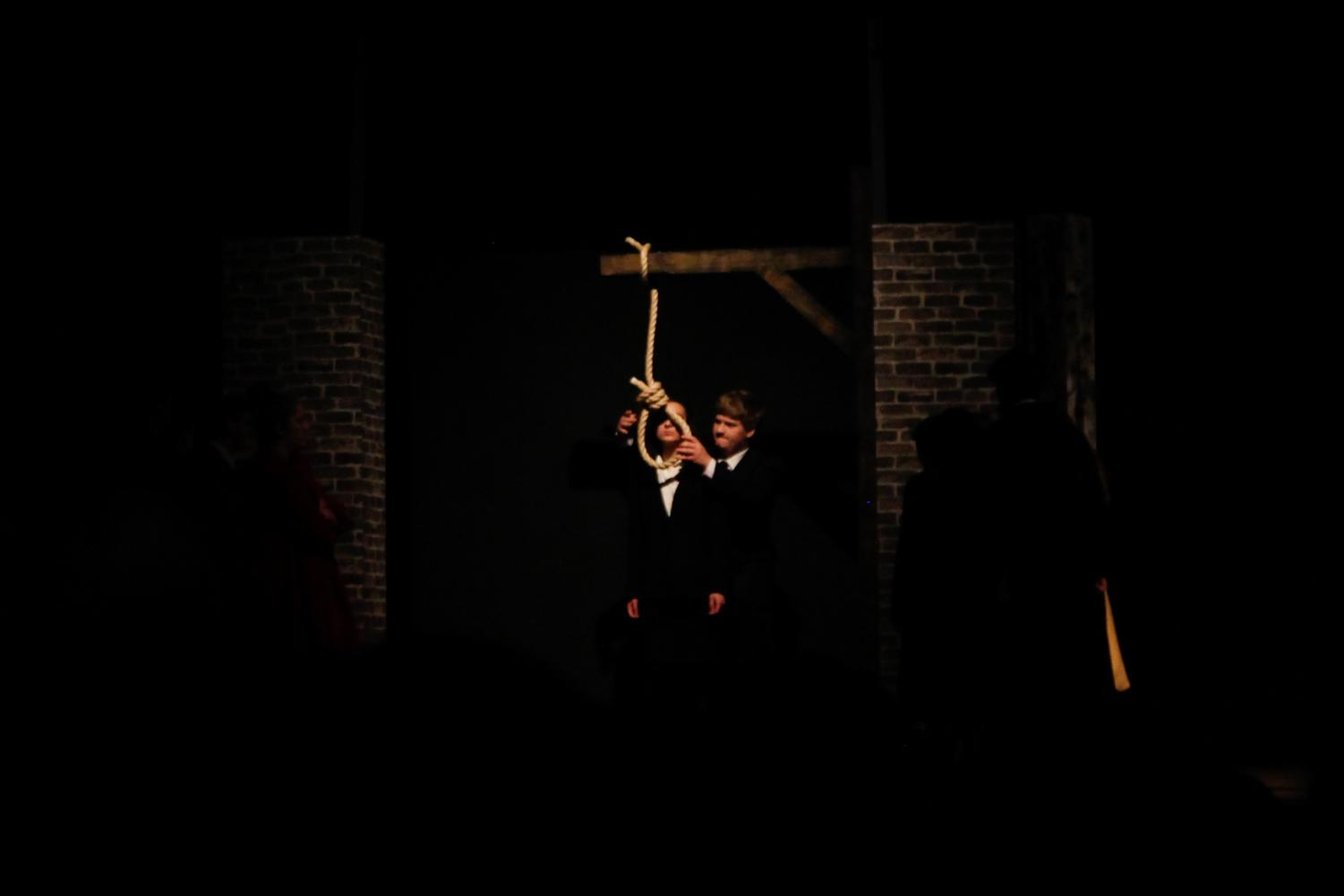 A guard (played by Steven Reis) prepares to hang Greta (played by Shea Kushnir) for her crimes against humanity.