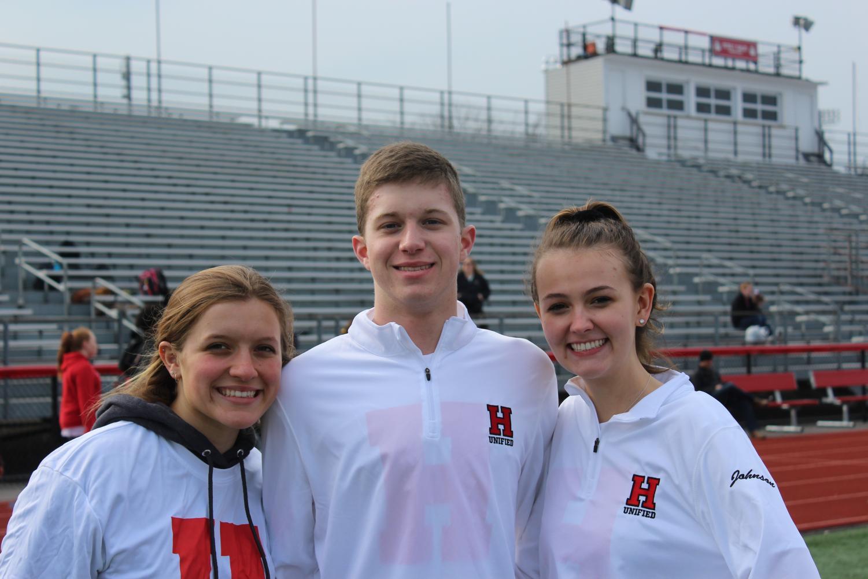 Junior Laine Skamarycz, freshman Mitch Wilson, and junior Zoe Johnson smile at their meet.