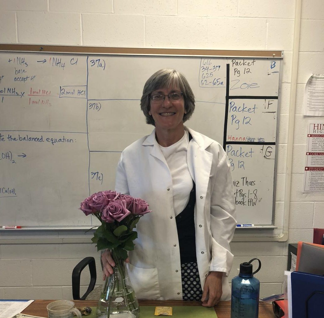 Mrs. Whitney smiles in front of a white board of practice problems in her classroom.