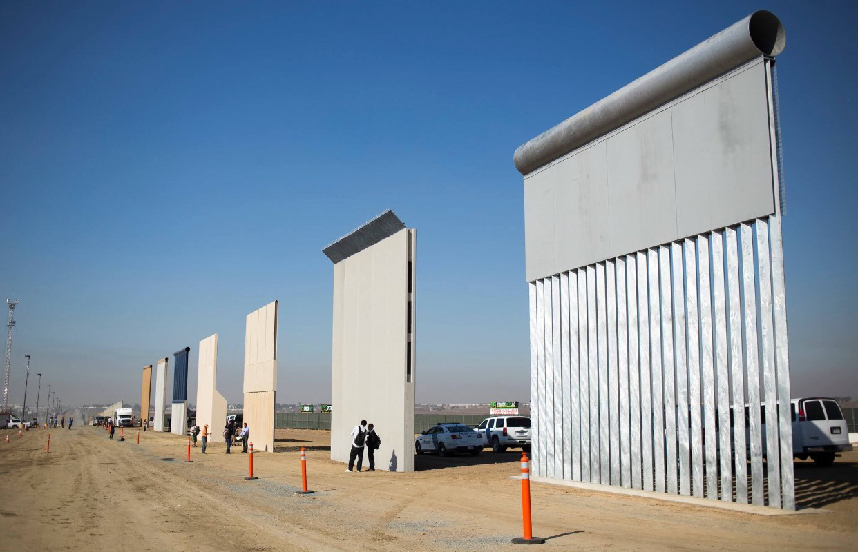 A display showing prototypes of the border wall. (Jenna Schoenefeld / The New York Times)