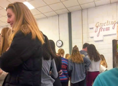 Students line up in the cafeteria to purchase rose and candy package for their friends before Valentine's Day.