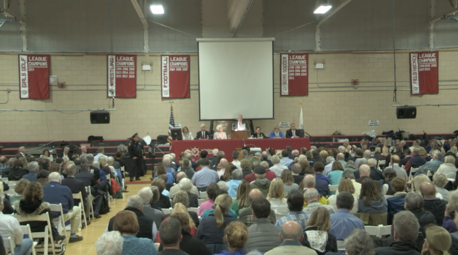 Town+Moderator+Mike+Puzo+reads+the+results+of+the+ballot+vote+on+Article+10.+%28Still+by+Harbor+Media%29