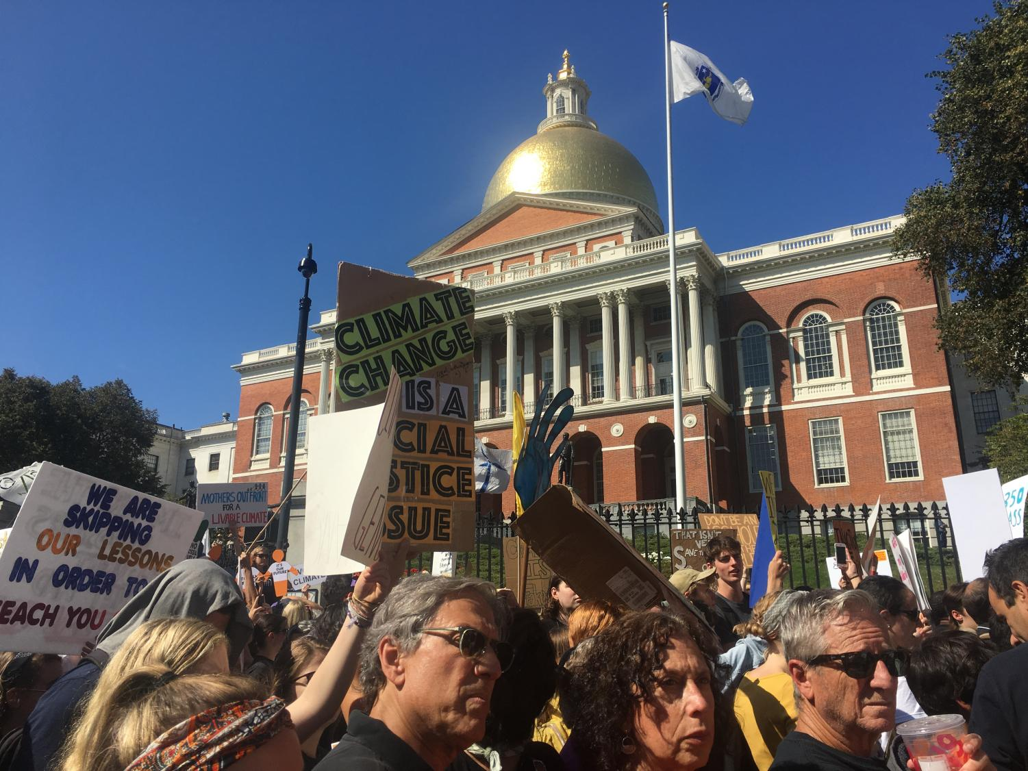 Protestors pass the Massachusetts State House.