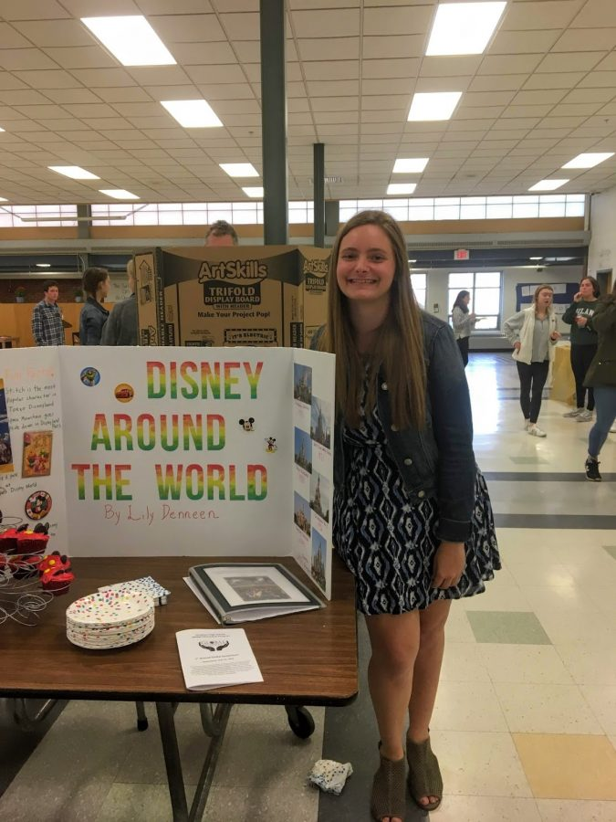 Hingham+High+School+Alumna+and+former+Global+Citizenship+Program+member+Lily+Deneen+stands+next+to+her+%22Disney+Around+the+World%22+portfolio+project+that+gained+her+a+Global+Competency+Certificate.+