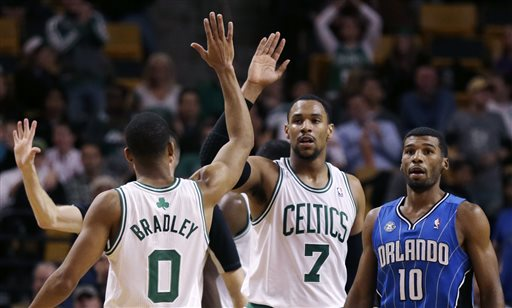 Boston Celtics forward Jared Sullinger (7) and guard Avery Bradley celebrate a point against the Orlando Magic during the second half of an NBA basketball game, in Boston, Monday, Nov. 11, 2013. The Celtics defeated the Magic 120-105. At right is Orlando Magic point guard Ronnie Price (10).