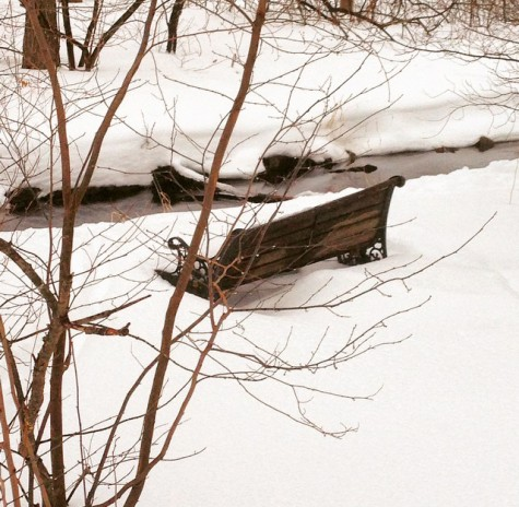 A bench situated on a scenic stream in Hingham, almost covered in a layer of snow.