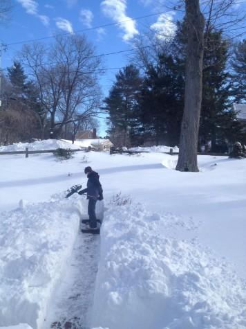 Hingham resident Tim Dwyer shovels a walkway.