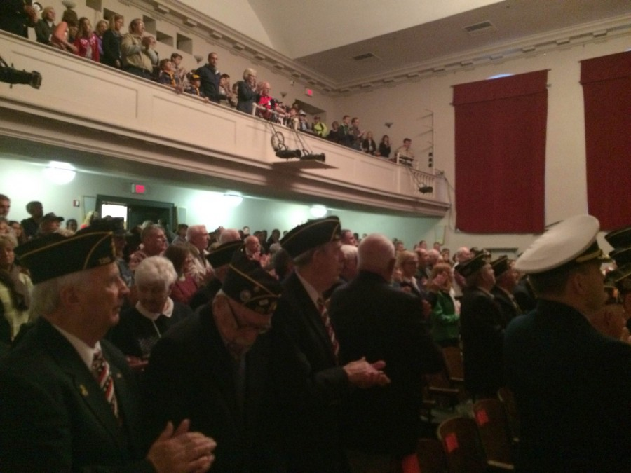 Veterans stand to commemorate their specific branch of service as its anthem is played by the band.