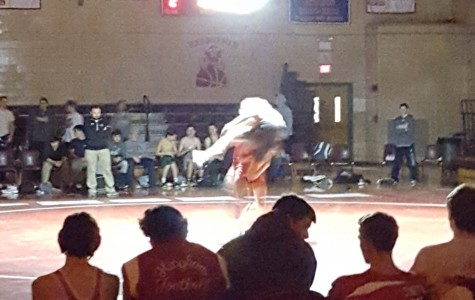 A Hingham wrestler throws Duxbury opponent on the ground