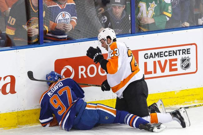 Rookie star Connor McDavid lies in pain after an awkward collision into the boards.
