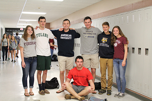 From left to right Meghan McConville, Matt Greene, Ryan Parker, Billy Harrington, Collin Parker, Ivan Frantz,  and Sarah Endyke all show of their college shirts on their long-awaited last day.