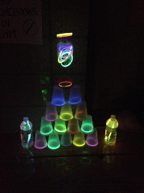 A pyramid formed out of cups and water bottles is adorned with glow bracelets.