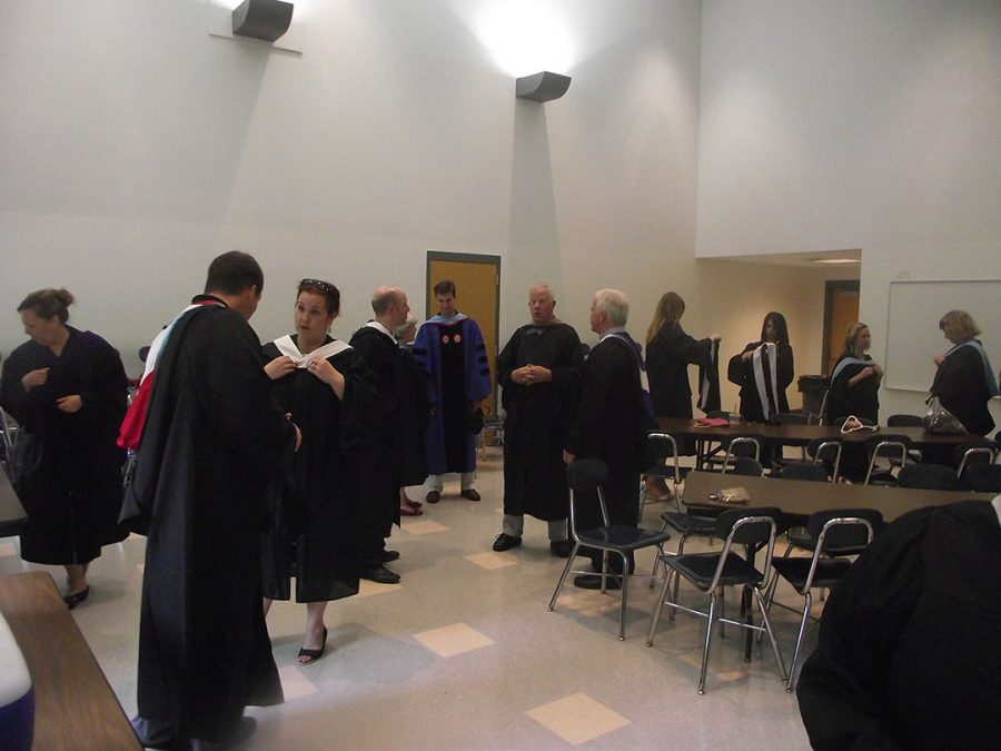 Teachers prepare their regalia robes before the ceremony begins.
