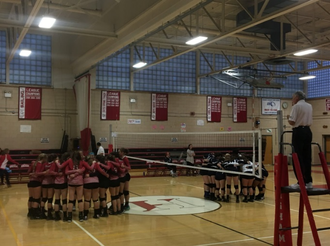 The volleyball teams in their huddle just before the game began.