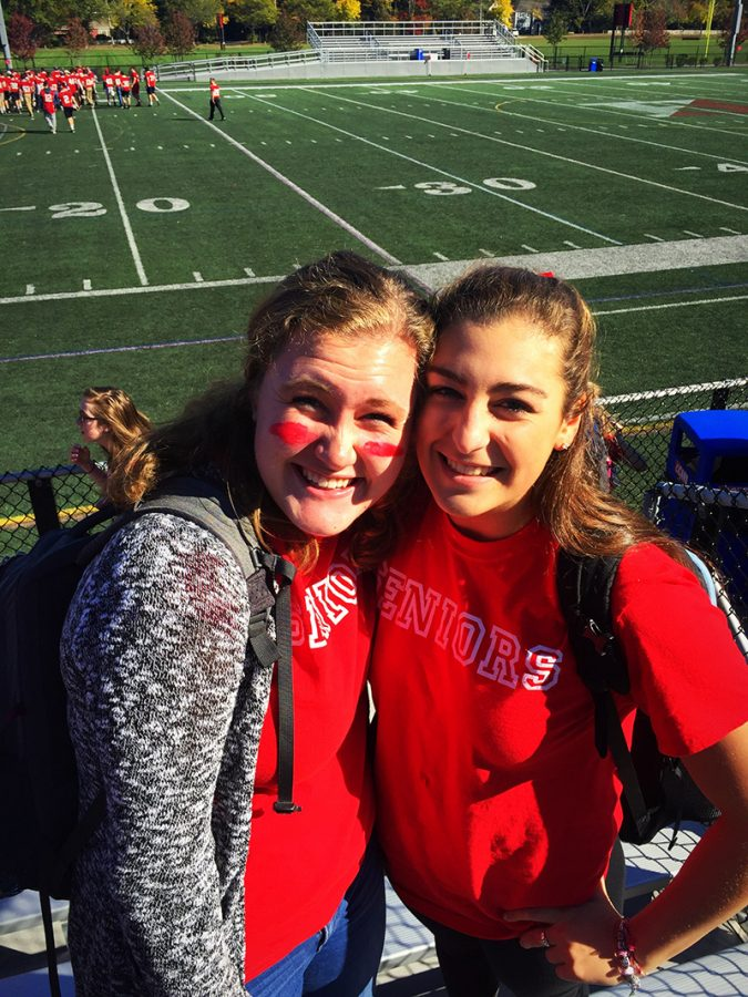 Seniors Steph Pett and Sarah Smith smile in the sunshine at one of their last pep rally's for Hingham High.