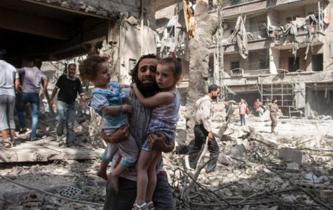 A Syrian man holds on tightly to his two young daughters as he stands in the rubble of a bombed neighborhood in al-Kalasa in  Aleppo.