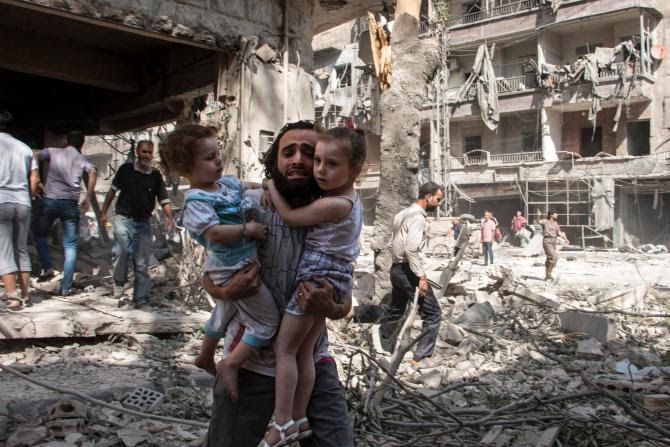 A+Syrian+man+holds+on+tightly+to+his+two+young+daughters+as+he+stands+in+the+rubble+of+a+bombed+neighborhood+in+al-Kalasa+in++Aleppo.