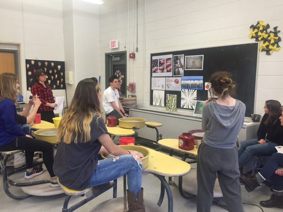 (From left) Claire Stone (Graphics III), Ms. Papuga (Ceramics Teacher), Anna Doggett (AP Studio), Cam Bonnell (AP Studio), and Lily Fernald (Portfolio) discuss Portfolio and Graphics III student Felicia Bornstein's (second from right) work