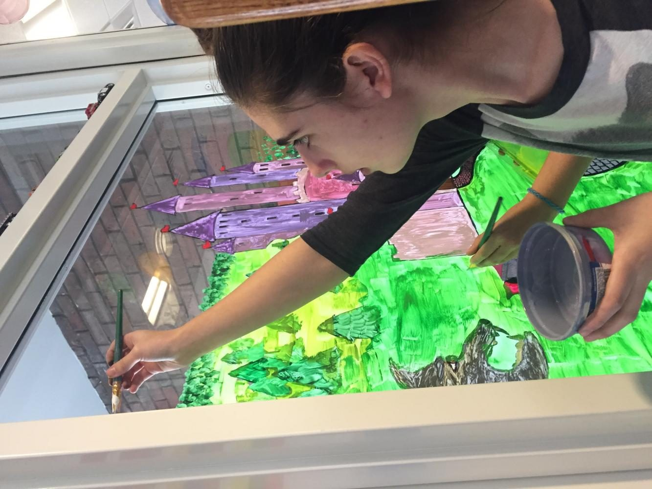 Freshman Gwen Moyer, a member of the art club, helps paint on a mural that the club created last month.