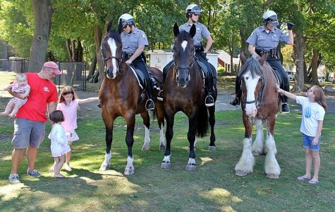 To the left, Recreational director Mike Bernard and his three little girls standing next to the Massachusetts State Police Horse Force.