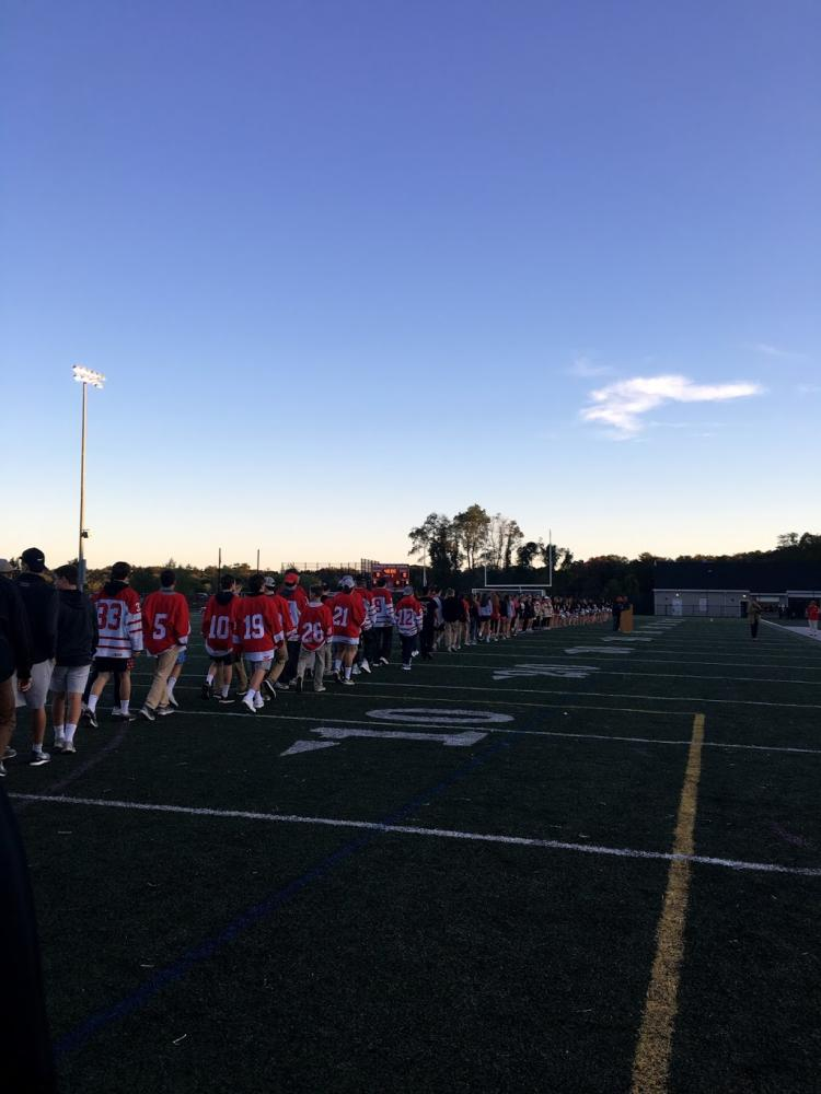 The Hingham High sports teams walk onto the soccer field before the game to support Mrs. Conaty.