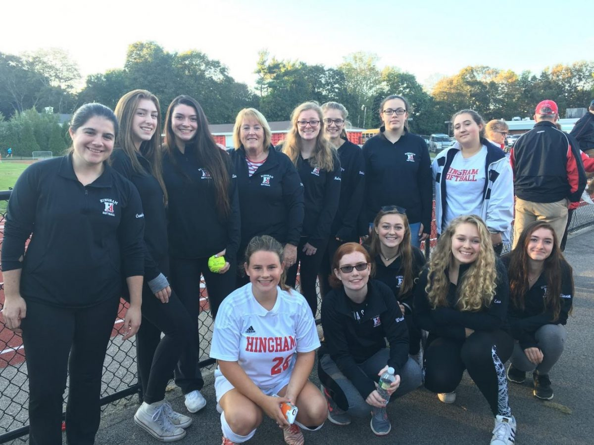 The Hingham Girls softball team gathers to support their fellow classmates on the field and celebrate the retirement of Maragret Conaty.