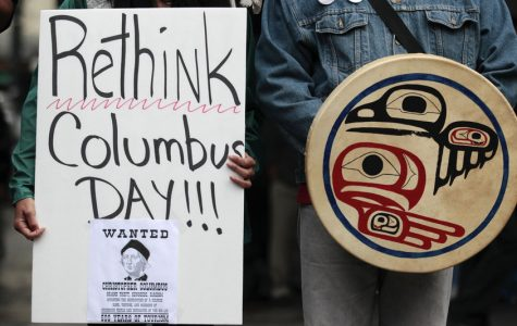 A sign held by a Native American protester publicly demonstrating against the celebration of Columbus Day in Seattle. Seattle later made the decision to replace the day with Indigenous Peoples'  Day in 2014.