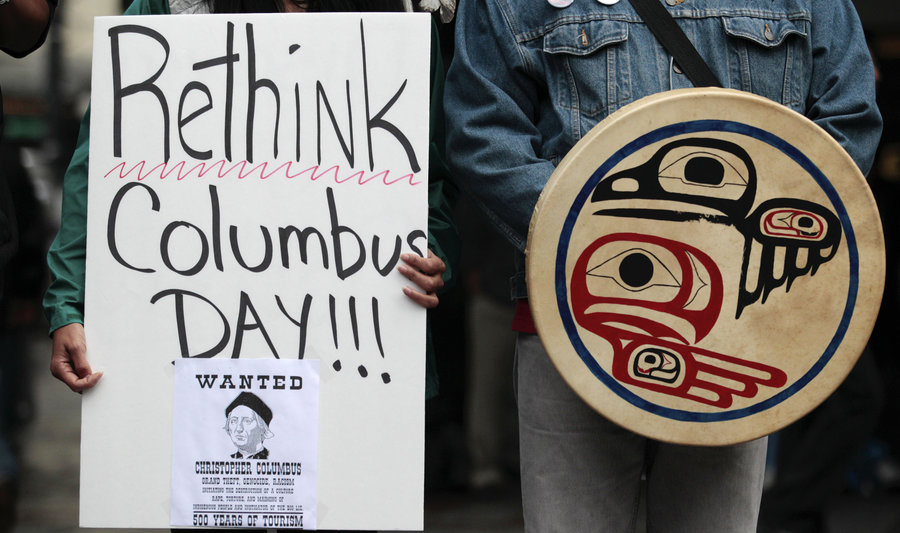 A+sign+held+by+a+Native+American+protester+publicly+demonstrating+against+the+celebration+of+Columbus+Day+in+Seattle.+Seattle+later+made+the+decision+to+replace+the+day+with+Indigenous+Peoples%27++Day+in+2014.+