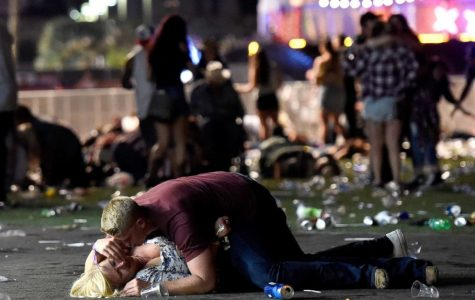 An unidentified man attempts to console a victim of the October 1 shooting. The woman survived. (David Becker/ Getty Images)