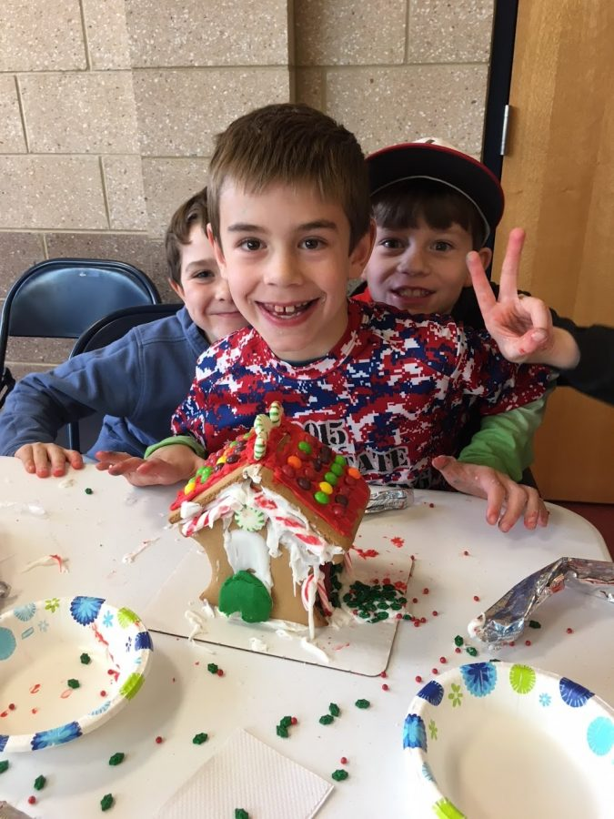 Sawyer Jacobson and friends pose before their gingerbread house.