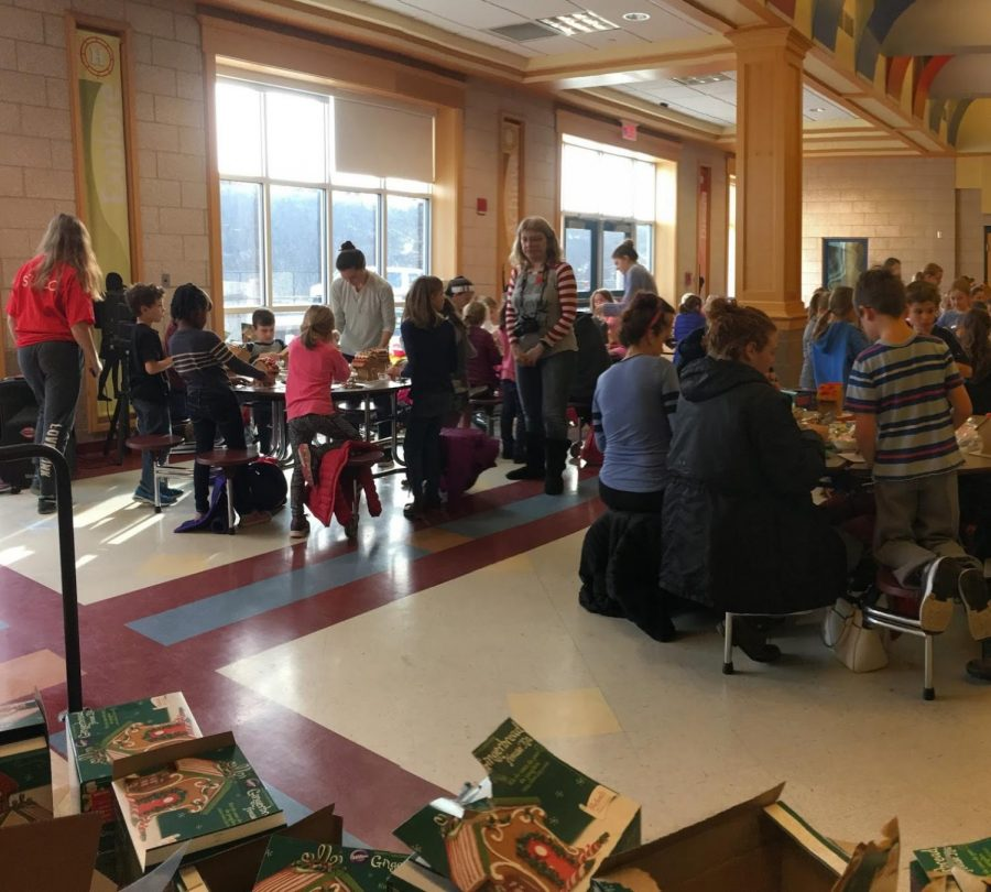 Hingham High Student Council members mingle with elementary school students, walking around and sitting down to help them.