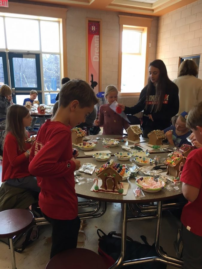 Student Council member Josie Ward helps elementary school students with icing.