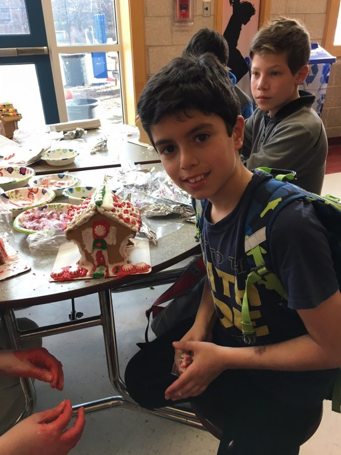 Fourth grader Noah Dell poses with his gingerbread house.