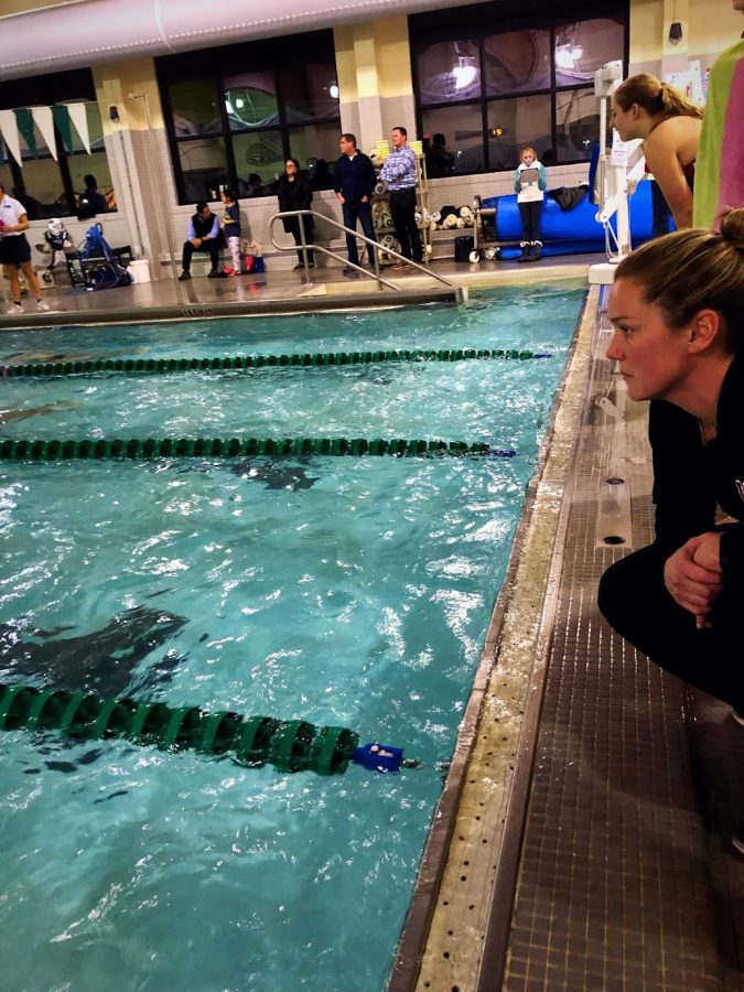 Assistant coach Kara McDonough cheers for her swimmers in the 400 relay.