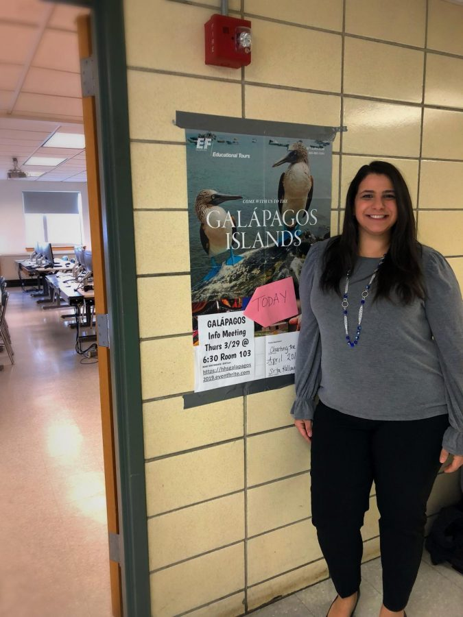 Señora Kelley poses in front of her Galápagos informational poster.