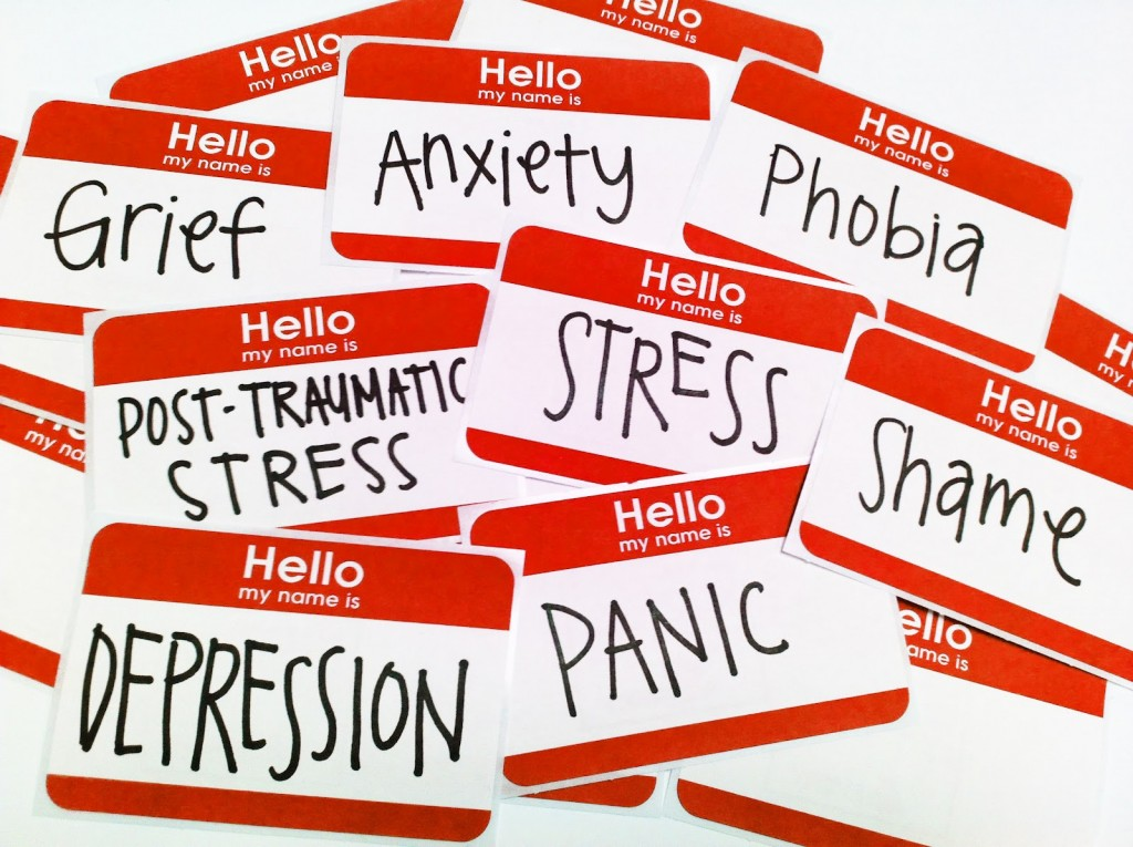 A pile of name tags with mental disorders written in place of names, emphasizing the ways in which society unfairly defines mentally ill people by their illnesses.