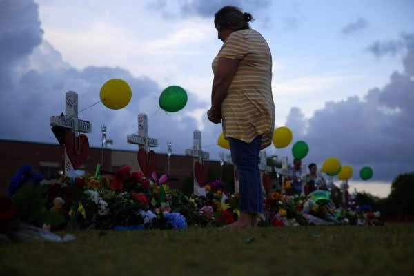 A mourner stands at the memorial for the 10 victims (Washington Post)