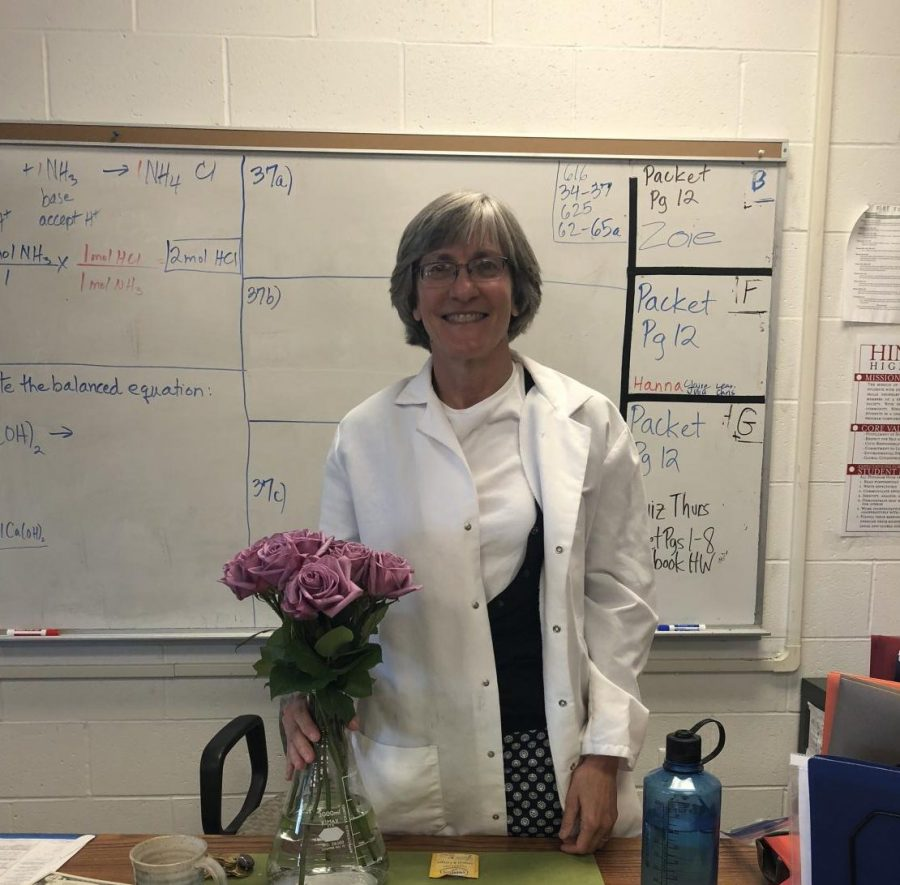 Mrs.+Whitney+smiles+in+front+of+a+white+board+of+practice+problems+in+her+classroom.