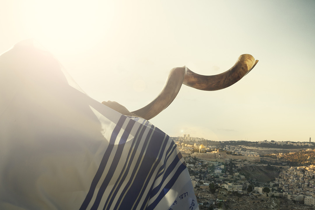 A Jewish man blows the shofar in honor of Rosh Hashanah.