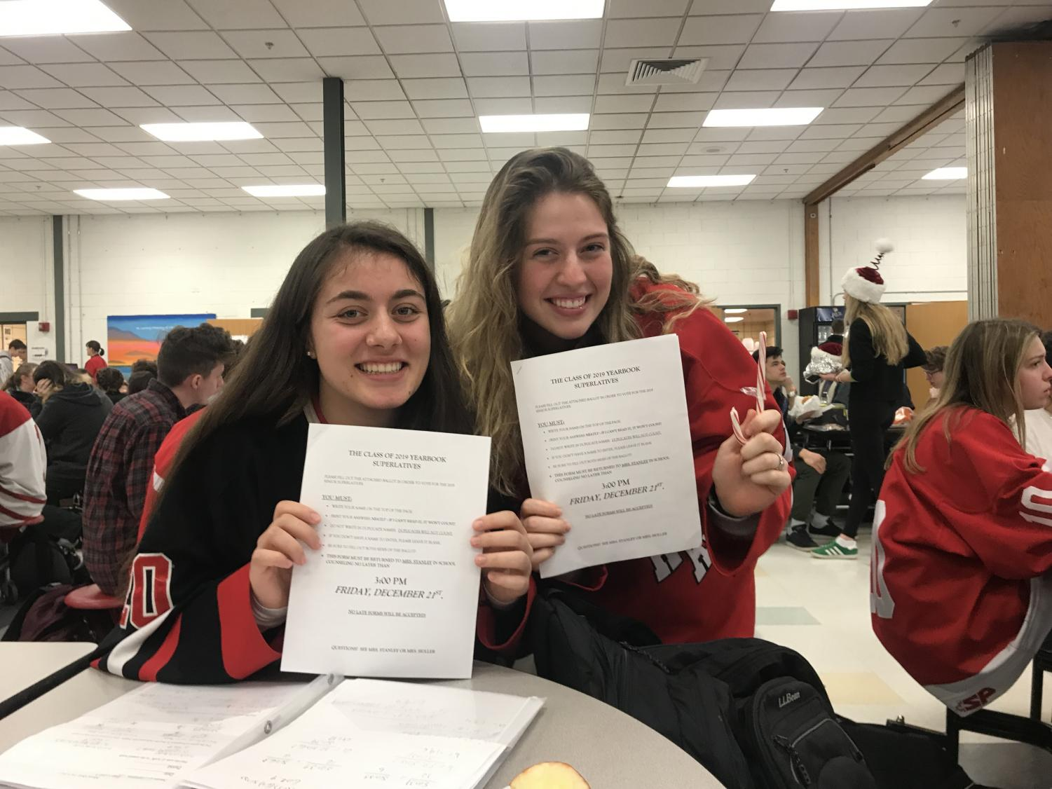 Seniors Gianna Merian and Aine Powell smile with their superlative voting forms.