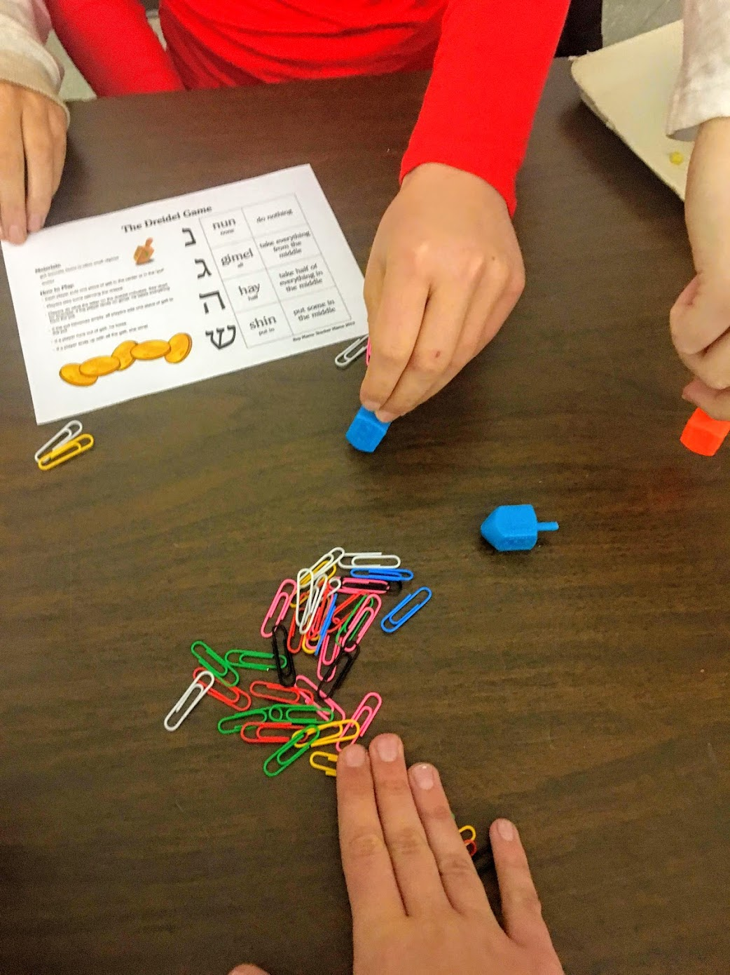 Members of the Global Citizenship Program play Dreidel during the Hanukkah Lunch Bunch on Monday.