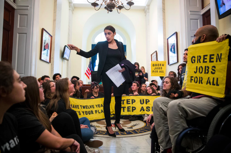 Alexandria Ocasio-Cortez praising climate change activists protesting outside of Nancy Pelosi's office. (Photo by Sarah Silbiger / The New York Times)