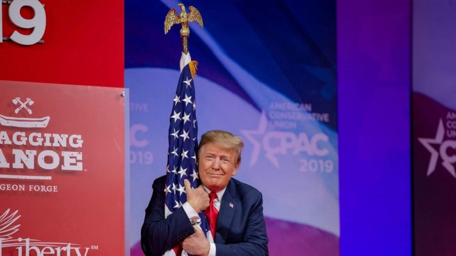 Trump hugging the US flag at the CPAC (Photo by Tasos Katopodis)