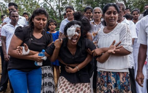 Mourners of the victims of the attacks in Sri Lanka break down while attending a mass burial in Negombo. (Adam Dean for the New York Times)