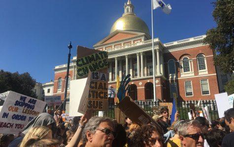 Protestors pass the Massachusetts State House.