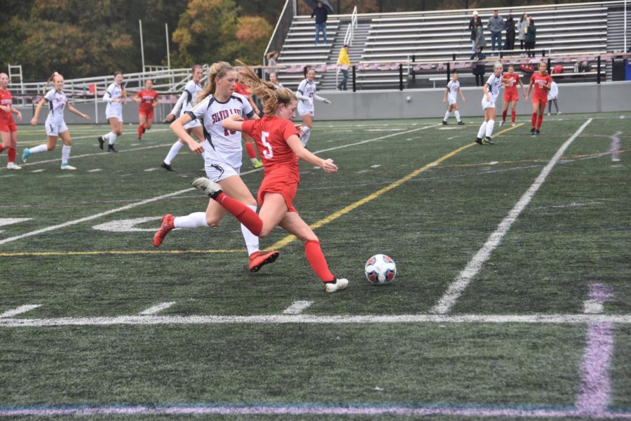 Sophomore Ava Maguire (#5) crosses the ball to switch fields.